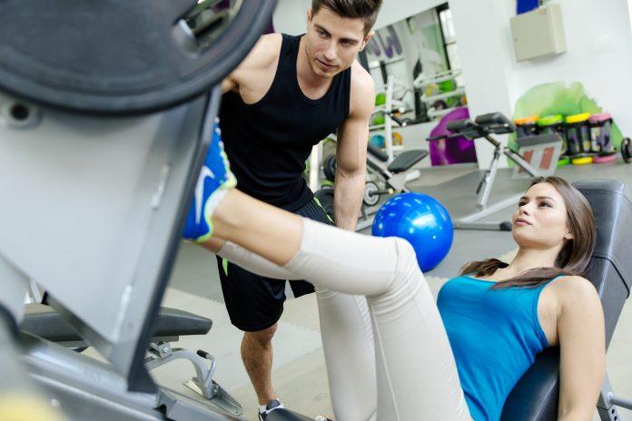 Przygotowanie motoryczne - kobieta ćwicząca w siłowni pod okiem trenera.