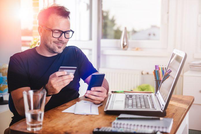 Uśmiechnięty mężczyzna, który korzysta z alertu BIK, aby ustrzec się przed kradzieżą danych